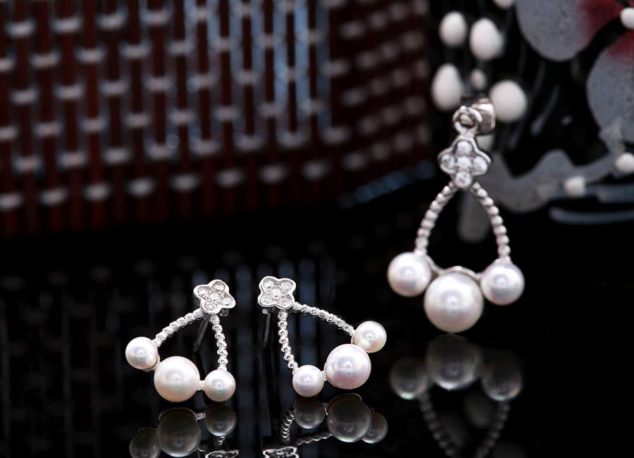 Đôi bông tai bạc gắn ngọc trai với sắc nét tạo hình ấn tượng.