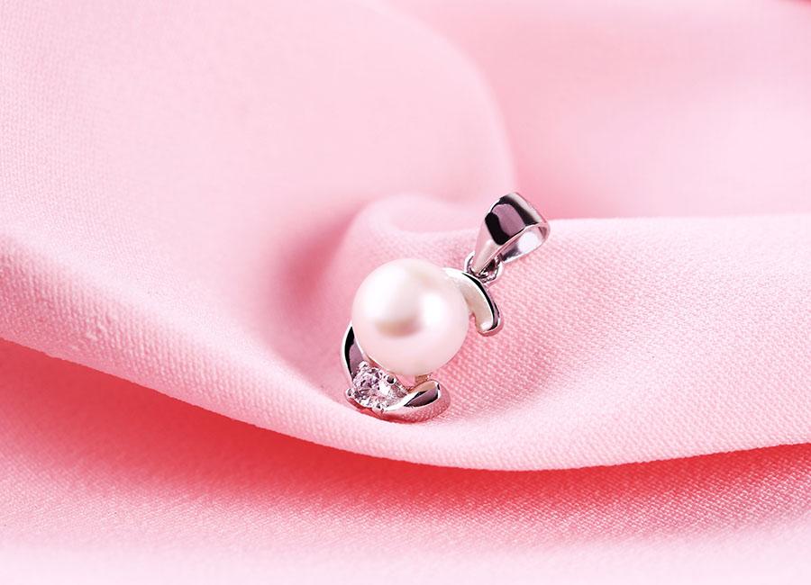 Cận cảnh mặt dây chuyền bạc với viên ngọc trai nằm chính giữa tạo điểm nhấn nổi bật.