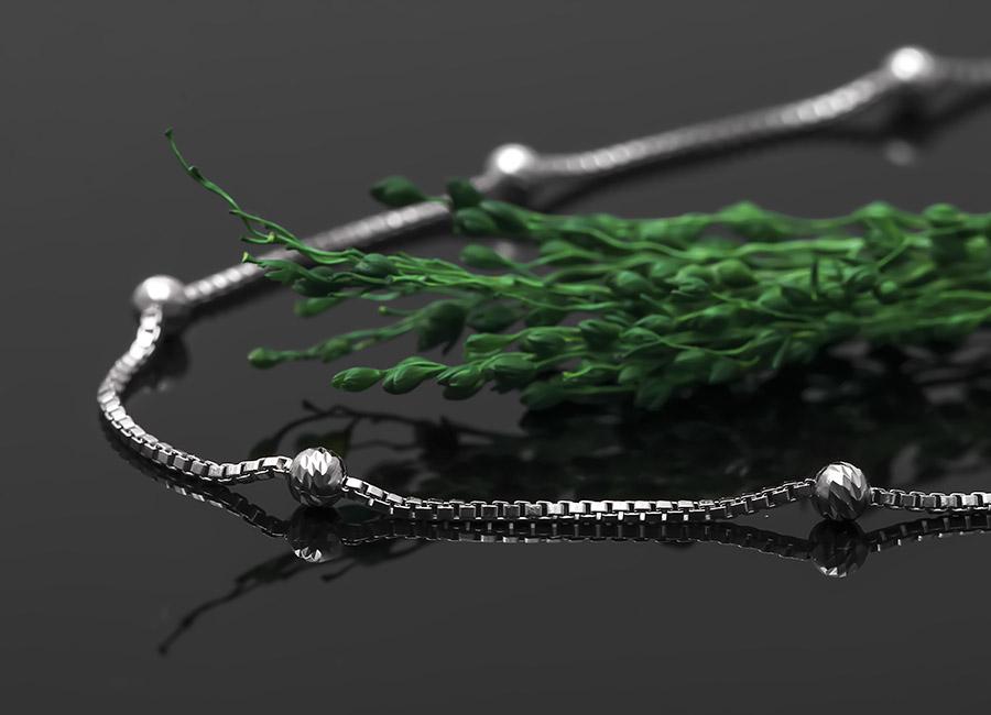 Thiết kế dạng mắt xích, chốt tròn điểm xuyết suốt chiều dài dây đeo.