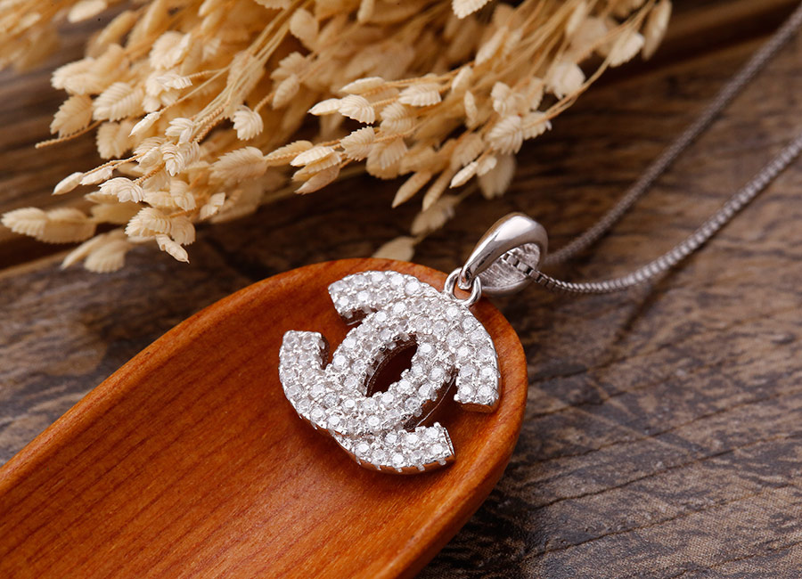 Đá CZ lung linh trong khuôn bạc tạo dáng logo Chanel.
