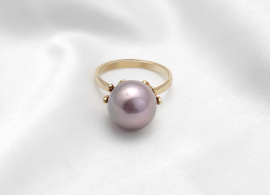 Những chiếc lá vàng đính thêm những viên kim cương ôm trọn lấy viên ngọc trai hồng.