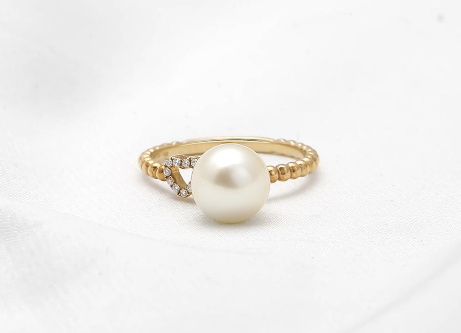 Mặt nhẫn tinh tế với viên ngọc trai thiên nhiên cùng trái tim đính kim cương nhỏ xinh.