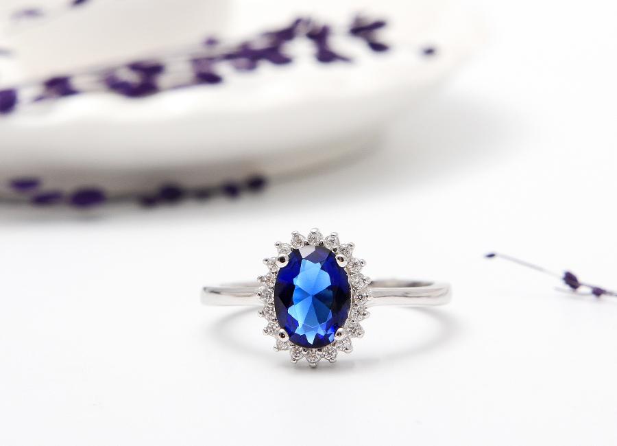 Viên đá xanh kiêu kỳ nằm trung tâm mặt nhẫn.