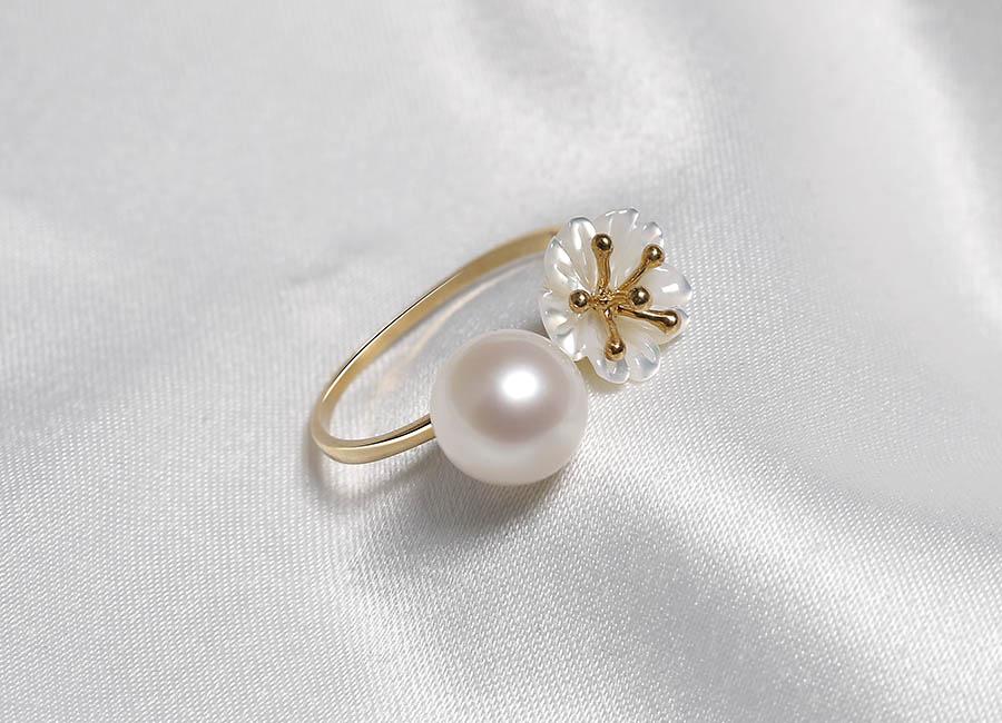 Chiếc nhẫn với thiết kế freesize đính hai đầu ngọc trai cùng bông hoa mai tạo nên một dáng nhẫn độc đáo.